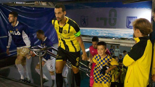 ילד מלווה את הקפטן דן איינבינדר בעלייה למשחק